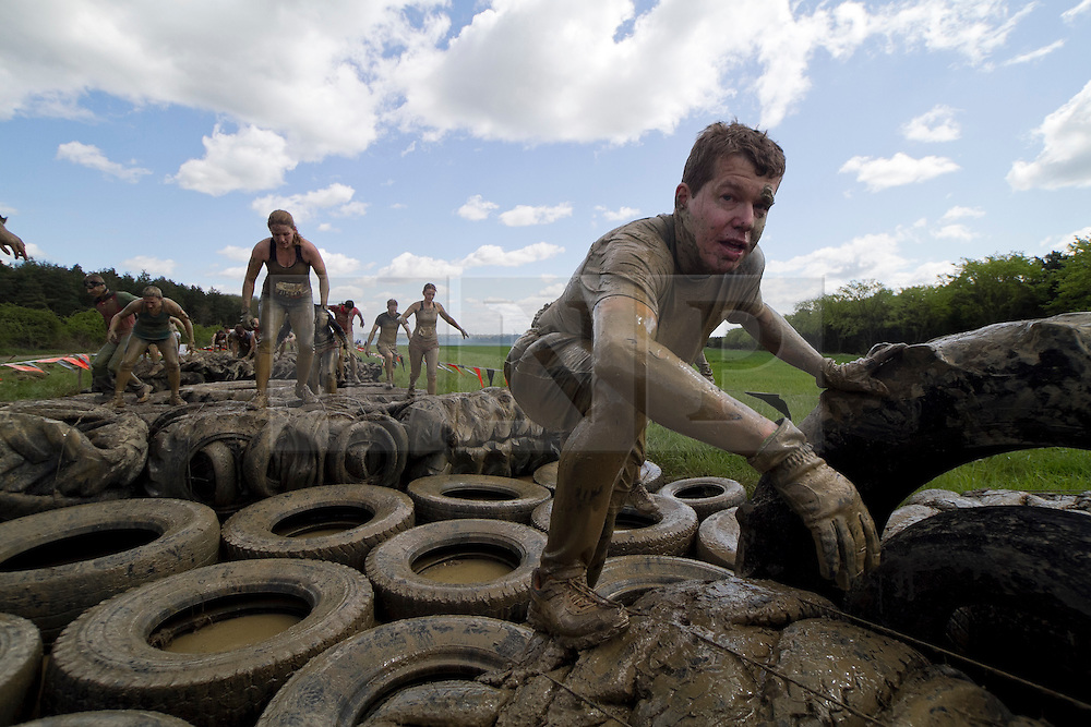 © Licensed to London News Pictures. 12/05/2012. Kettering, UK. A mud soaked Tough Mudder competitor works his way through a tyre filled obstacle. Thousands of people took part in Tough Mudder today (12/05) in the grounds of Boughton House, Northamptonshire. The 12 mile course which was designed by British special forces soldiers, consisted of 25 extreme obstacles including water, mud, electrocution, and high walls. The challenge is designed to test teamwork abilities as well as physical strength and stamina . Photo credit : James Gourley/LNP