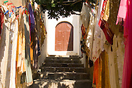 Colourful textiles for sale along steps approachig the Acropolis, Lindos, Rhodes, Dodecanese Islands, Greece