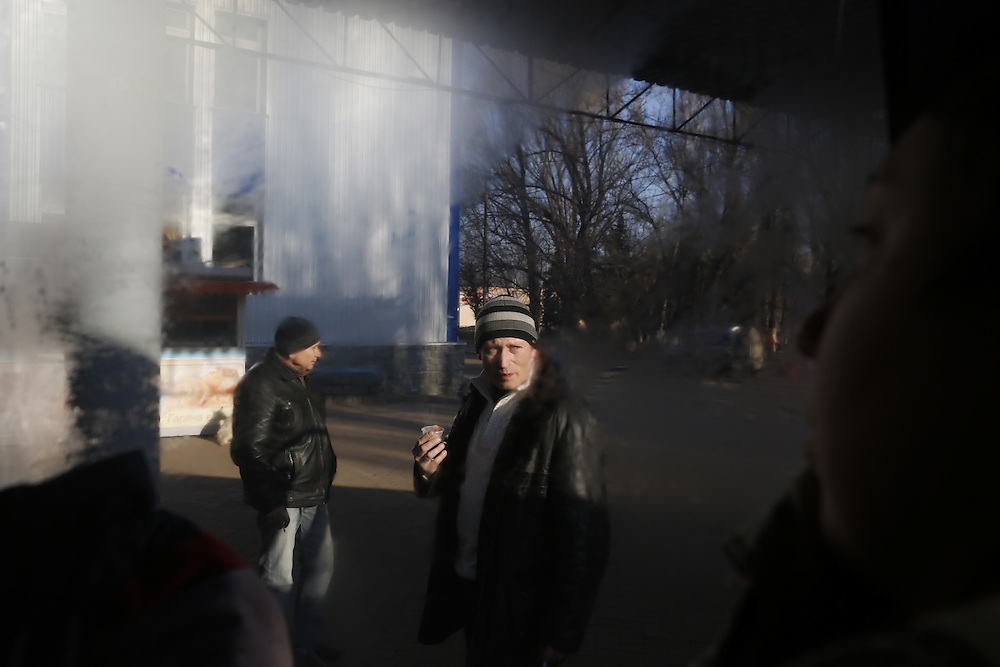 People are seen through a foggy window at a bus stop between Slavyansk and Artemivsk on February 13, 2015.