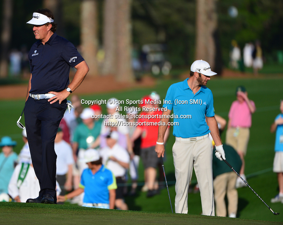 April 9, 2013 - Augusta, Georgia, U.S. - Phil Mickelson, left, and Dustin Johnson on the 2 green during the second practice round of the 2013 Masters Tournament at Augusta National Golf Club on April 9, 2013, in Augusta, Ga.