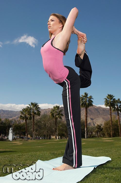 Young woman performing yoga exercises in park