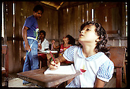 Girl gazes at blackboard at jungle school for rubber tappers' kids on Seringal Cachoeira, Acre Brazil