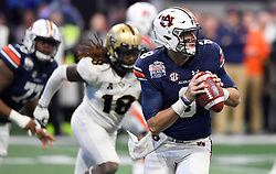 Auburn Tigers quarterback Jarrett Stidham (8) scrambles under pressure from the Central Florida University defenders during the second half of the Chick-fil-A Peach Bowl NCAA college football game at the Mercedes-Benz Stadium in Atlanta, January 1, 2018. UCF won 34-27 to go undefeated for the season. (David Tulis via Abell Images for Chick-fil-A Peach Bowl)