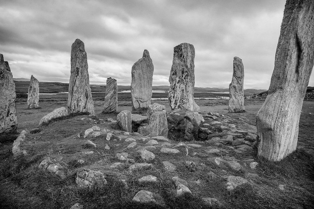 The Callanish Stones (Clachan Chalanais or Tursachan Chalanais in Gaelic) are an arrangement of standing stones placed in a cruciform pattern with a central stone circle. They were erected in the late Neolithic era, and were a focus for ritual activity during the Bronze Age. They are near the village of Callanish (Calanais) on the on the North East edge of The Isle of Lewis in the Outer Hebrides, Scotland.<br /> <br /> This photograph is a monochramatic version of the view of the Callanish Standing Stones on the Isle of Lewis. The photograph can be purchased as print, mounted print in frames, canvas or aluminum or as a digital file.