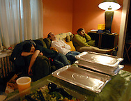 "December 4, 2009- Having worked 13 hours straight, lighting assistants, juniors Max Gosselin-Ildari (left) and Peter Horgan (center), also known as ""grips,"" along with homeowner Francine Smith, catch a few minutes of rest in-between shots on the set of ""The Last Laugh"" in Dorchester, MA. ""As grips we barely get to rest, so if I see an opportunity I make sure to take it,"" said Horgan."