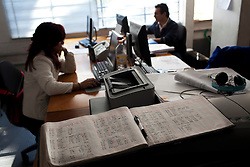The staff sign in book sits in the foreground as workers work in the background Inside the office of  Arquitectura 911Sc  in Mexico City.