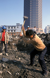 CHINA SHANGHAI PUDONG MAY99 - A Chinese construction worker crushes stones while his colleagues look on in Pudong. Pudong has experienced a dramatic rise in construction projects, although vacancy rates stand at nearly 60% and a bust-cycle is imminent. .. jre/Photo by Jiri Rezac..© Jiri Rezac 1999..Contact: +44 (0) 7050 110 417.Mobile:  +44 (0) 7801 337 683.Office:  +44 (0) 20 8968 9635..Email:   jiri@jirirezac.com.Web:     www.jirirezac.com..© All images Jiri Rezac 1999 - All rights reserved.