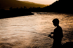 United States, Montana, Yellowstone National Park, Lamar River, silhouette of boy (age 7) fishing at sunset.  MR