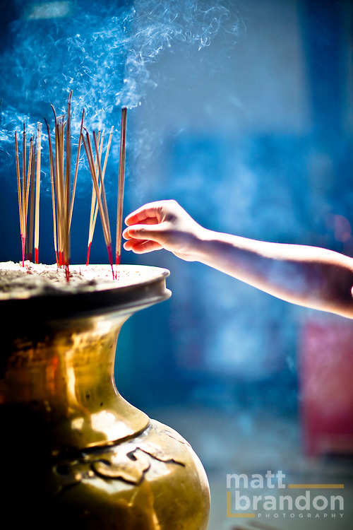 A woman's hand draws away after placing a joss stick in the sand and the Chinese temple.