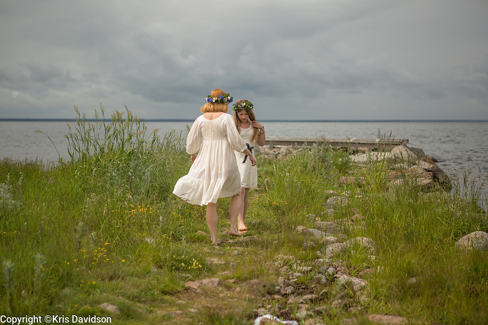 Girl with her mother on Öland, a Swedish island in the Baltic Sea, during the Midsummer holiday. The longest day of the year is a beloved holiday in Sweden; the cities are empty as the locals take to the countryside for a day of dancing and singing with family and friends.