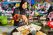 10 JULY 2013 - PATTANI, PATTANI, THAILAND:  A Muslim women makes roti to sell for Iftar in a market near Krue Se Mosque in Pattani, Thailand. Iftar is the meal Muslims take when they break their daily Ramadan fast. Ramadan is the ninth month of the Islamic calendar, and the month in which Muslims believe the Quran was revealed. Muslims believe that the Quran was sent down during this month, thus being prepared for gradual revelation by Jibraeel (Gabriel) to the prophet Muhammad.  The month is spent fasting during the daylight hours from dawn to sunset. Fasting during the month of Ramadan is one of the Five Pillars of Islam.     PHOTO BY JACK KURTZ