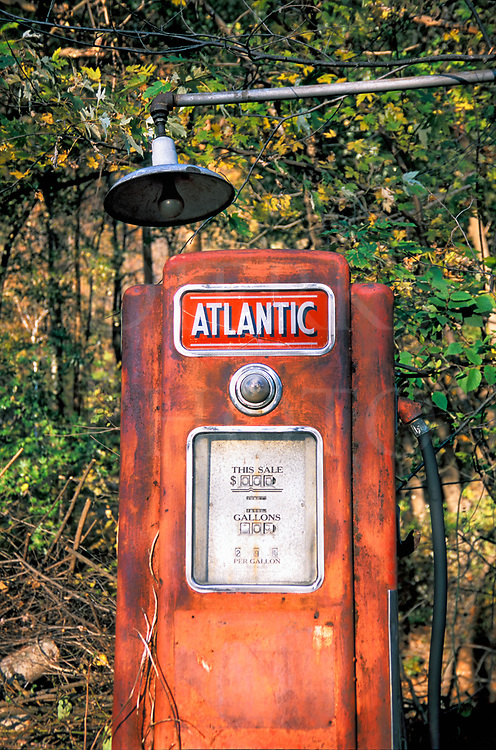 A rusty Atlantic gas pump at a small closed up country gas station sitting out in the jingweeds of rural Pennsylvania. The price on the vintage pump: 29 cents a gallon.