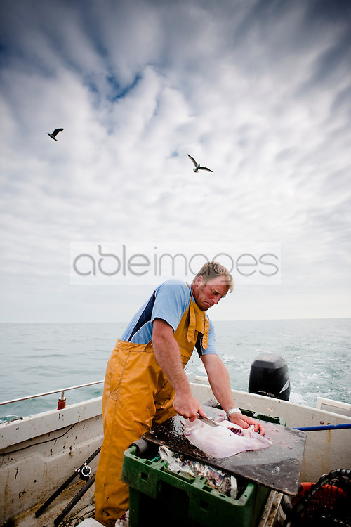 Fisherman standing in a boat cutting a fish
