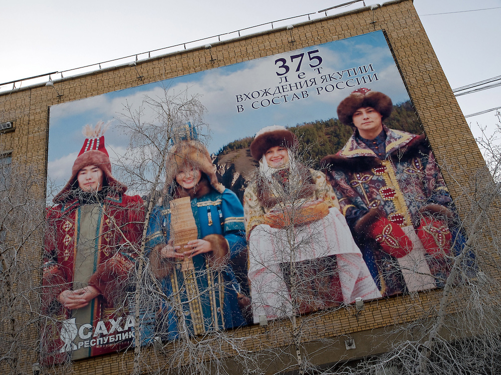 Plakatwand in Jakutsk. Jakutsk wurde 1632 gegruendet und feierte 2007 sein 375 jaehriges Bestehen. Jakutsk ist im Winter eine der kaeltesten Grossstaedte weltweit mit durchschnittlichen Winter Temperaturen von -40.9 Grad Celsius. Die Stadt ist nicht weit entfernt von Oimjakon, dem Kaeltepol der bewohnten Gebiete der Erde.<br /> <br /> Billboard in the city center of Yakutsk. Yakutsk was founded in 1632 and celebrated 2007 the 375th anniversary - billboard announcing the celebration. Yakutsk is a city in the Russian Far East, located about 4 degrees (450 km) below the Arctic Circle. It is the capital of the Sakha (Yakutia) Republic (formerly the Yakut Autonomous Soviet Socialist Republic), Russia and a major port on the Lena River. Yakutsk is one of the coldest cities on earth, with winter temperatures averaging -40.9 degrees Celsius.
