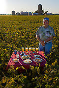 Gordon Stine, a farmer, with his typical day's worth of food in his family's soybean field in St. Elmo, Illinois. (From the book What I Eat: Around the World in 80 Diets.) The caloric value of his day's worth of food in the month of September was 4,100 kcals. He is 56 years old; 5 feet, 9 inches tall; and 245 pounds. MODEL RELEASED.