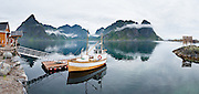 A boat anchors in Reinefjord at the tiny island fishing village of Sakrisøy, which is connected by bridge to Reine on Moskenesøya (The Moskenes Island) and to Hamnøy in the Lofoten archipelago, Nordland county, Norwegian Sea, Norway. Sharply glaciated peaks rise above the Norwegian Sea. Panorama stitched from 7 overlapping photos.