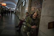 Man huddled on bench in Kyiv Metro.  Kyiv, Ukraine