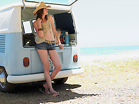 Young woman leaning on open tailgate of camper van parked by sea