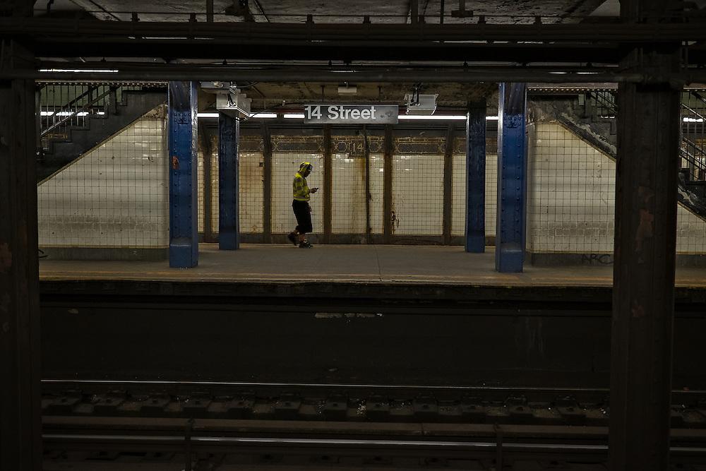 Man in stripes walking on 14th Street subway platform, New York, NY, US