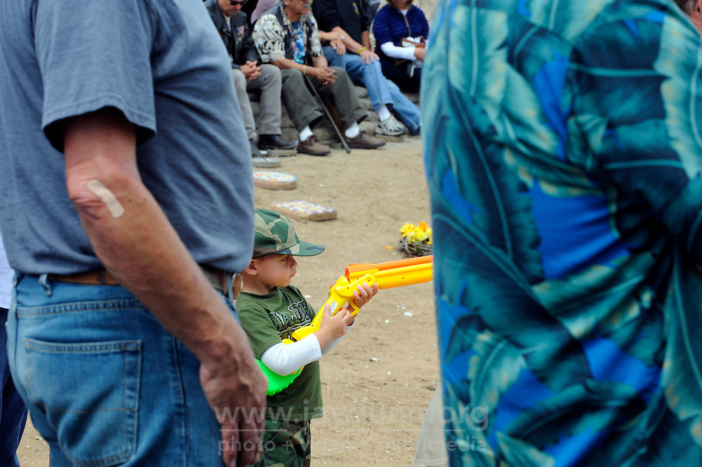 A young soldier plays with a shotgun during Monday's somber Memorial Day remembrances at the Monterey County Vietnam Veterans Memorial in Salinas.