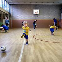 Nederland, Amsterdam , 30 maart 2013.<br /> voetballes voor 2 en 3 jarige kinderen op de 2e Daltonschool in Amsterdam Zuid.<br /> Onderdeel van de voetballes zijn oefeningen waarbij vooral motoriek een belangrijke rol speelt.<br /> Football lesson for 2 - and 3-year-old children in a gymnasium in Amsterdam