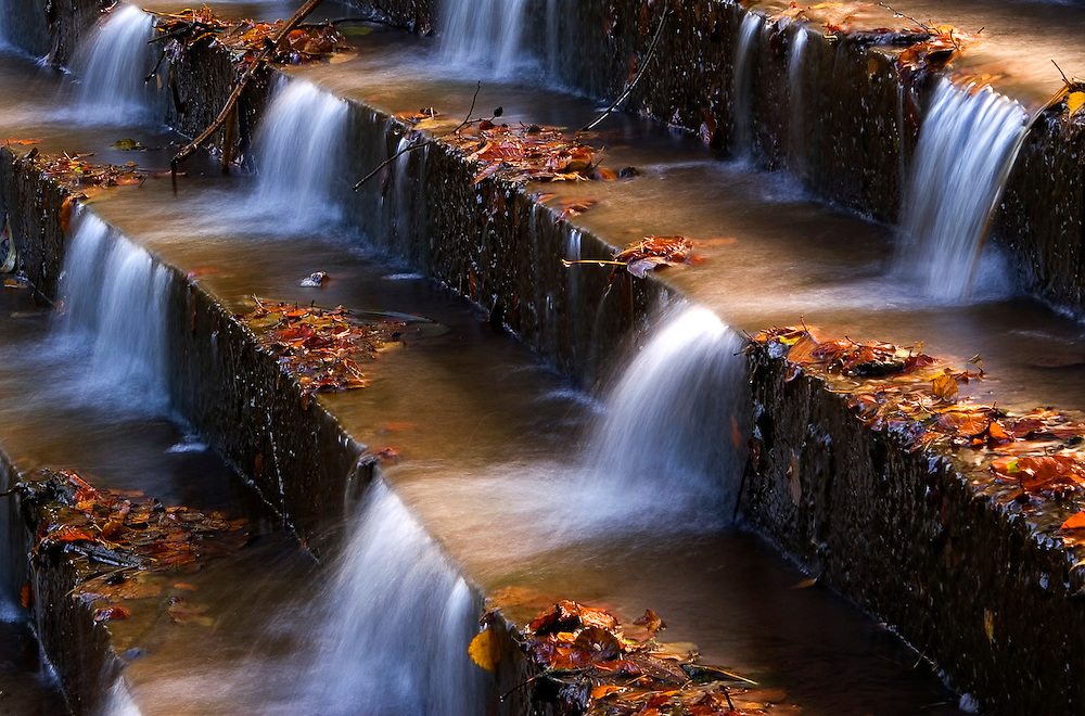 Autumn leaving its litter on the steps works perfectly, with the trio of waterfalls working their way down.
