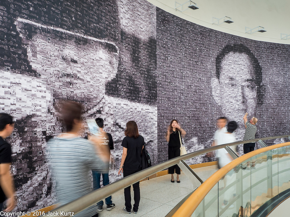 "06 NOVEMBER 2016 - BANGKOK, THAILAND: Thais walk past large mosaic photos of Bhumibol Adulyadej, the late King of Thailand at the Bangkok Art and Culture Centre. The Royal Photographic Society of Thailand with the Bangkok Art and Culture Centre and Thai Beverage Public Company Limited are hosting a photography exhibition to commemorate the late Thai King Bhumibol Adulyadej. The ""In Remembrance of His Majesty King Bhumibol Adulyadej"" Photography Exhibition is dsiplaying 89 photographs by 89 photographers honoring King Bhumibol Adulyadej's legacy. The King was an avid photographer was usually seen with a camera in his hands. The exhibition will be on display until 27 November 2016 on the Curved Walls on the 3rd - 5th floor, Bangkok Art and Culture Centre.     PHOTO BY JACK KURTZ"