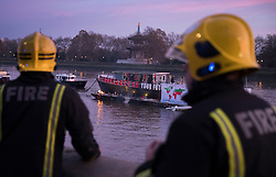 "© Licensed to London News Pictures. 26/11/2016. London, UK. Firemen watch a fire started by Joe Corre, the son of former Sex Pistol manager Malcolm McLaren and Vivienne Westwood as he burns his personal collection of Sex Pistols punk memorabilia on a boat in the Thames in Chelsea. Earlier this week Joe Corre said that punk has become nothing more than a ""McDonald's brand ... owned by the state, establishment and corporations"". His collection is estimated to be worth £5 million. Photo credit: Peter Macdiarmid/LNP"