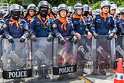 07 AUGUST 2013 - BANGKOK, THAILAND:     Thai riot police close a road to prevent anti-government protesters from going to the Parliament building. About 2,500 protestors opposed to an amnesty bill proposed by Thailand's ruling party marched towards the Thai parliament in the morning. The amnesty could allow exiled fugitive former Prime Minister Thaksin Shinawatra to return to Thailand. Thaksin's supporters are in favor of the bill but Thai Yellow Shirts and government opponents are against the bill. Thai police deployed about more than 10,000 riot police and closed roads around the parliament. Although protest leaders called off the protest rather than confront police, a few people were arrested for assaulting police when they tried to break through police lines. Several police officers left the scene under medical care after they collapsed in the heat.     PHOTO BY JACK KURTZ