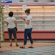 OCTOBER 18 - LARES, PUERTO RICO - <br /> Mercy Corps staffers Alexa Swift, right, and Jasmine Avgerakis inspect items on shelves in a Mr. Special Supermarket in Lares as part of their field research on Puerto Rico's supply needs following the destructive path of hurricane Maria.<br /> (Photo by Angel Valentin for NPR)