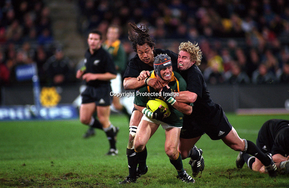 Marius Joubert is tackled during the rugby union Tri Nations test match between the All Blacks and South Africa, Wesptac Trust Stadium, Wellington, 20 July, 2002. Photo: PHOTOSPORT
