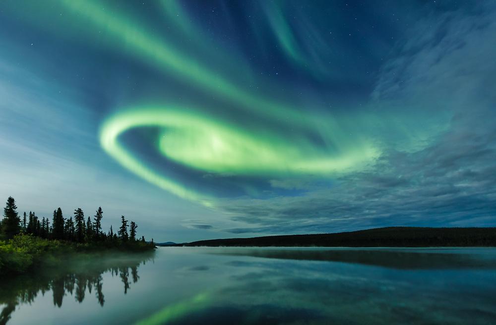Aurora Borealis over Paxson Lake in Interior Alaska. Summer. Evening.