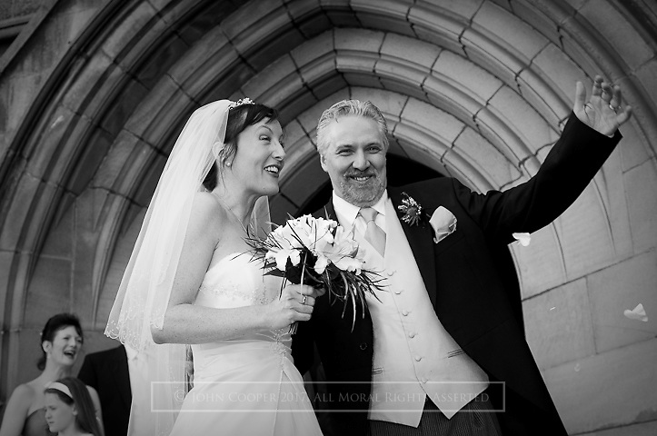 Wedding couple laughing outside Peebles Old Parish Church.