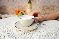 Cropped image of man having cup of coffee at table in cafe