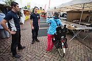Wouter Horstink (links) en Timo Westerhoff spreken op de markt een vrouw met een fiets aan. In Leusden zorgen studenten van de ROC A12 opleiding Veiligheid & Toezicht als stagiair voor toezicht en handhaving in het winkelcentrum De Biezenkamp. De ondernemers in het winkelcentrum bepalen welke taken de studenten krijgen, de politie en een buitengewoon opsporingsambtenaar begeleiden de studenten.