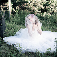 Female youth with sad expression wearing white dress sitting in graveyard