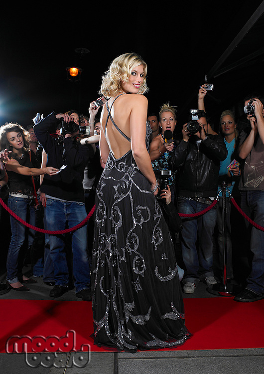 Woman posing on red carpet in front of fans