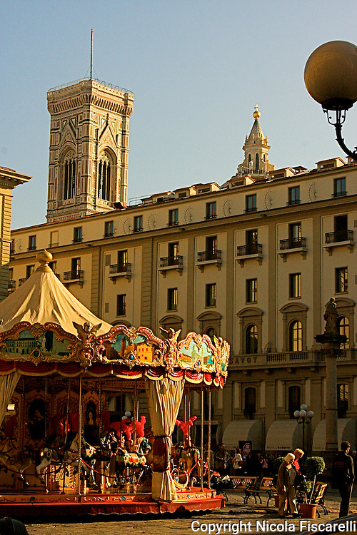 The view of the carousel in the Piazza della Republica with the  Campanile di Giotto in the background ,in center city of Florence.