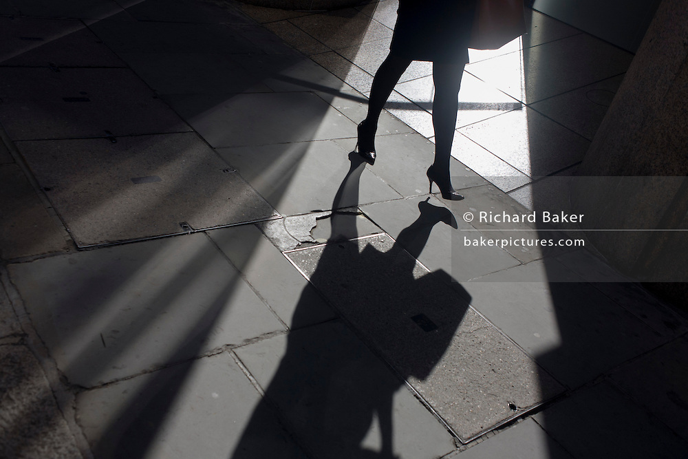 A professional-looking businesswoman walks through sunlight in a City of London street.