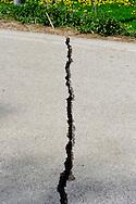 Onna  10 Aprile 2009.Terremoto Abruzzo.Macerie nelle vie del paese devastato dal terremoto.Una strada spaccata dal terremoto.A pile of rubble  in the main street of the devastated small village, a crack in a road  ..