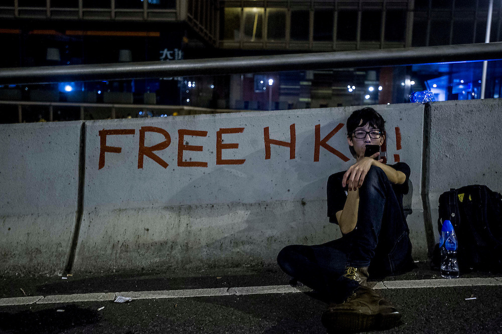 A protester takes a rest during riots that followed a pro-democracy protest in Hong Kong on September 28, 2014. Police fired tear gas as tens of thousands of pro-democracy demonstrators brought parts of central Hong Kong to a standstill in a dramatic escalation of protests that have gripped the semi-autonomous Chinese city for days. AFP PHOTO / XAUME OLLEROS