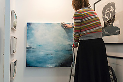 """© Licensed to London News Pictures. 17/01/2017. London, UK. A gallery owner hangs """"Ocean Light Rising"""" by Gareth Edwards at the preview of the 29th London Art Fair, the UK's premier fair for Modern British and contemporary art, taking place at the Business Design Centre in Islington from 18-22 January 2017, where 129 galleries from 18 different countries will be presenting their artworks. Photo credit : Stephen Chung/LNP"""
