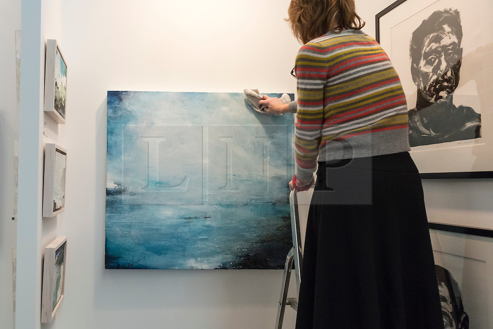 "© Licensed to London News Pictures. 17/01/2017. London, UK. A gallery owner hangs ""Ocean Light Rising"" by Gareth Edwards at the preview of the 29th London Art Fair, the UK's premier fair for Modern British and contemporary art, taking place at the Business Design Centre in Islington from 18-22 January 2017, where 129 galleries from 18 different countries will be presenting their artworks. Photo credit : Stephen Chung/LNP"