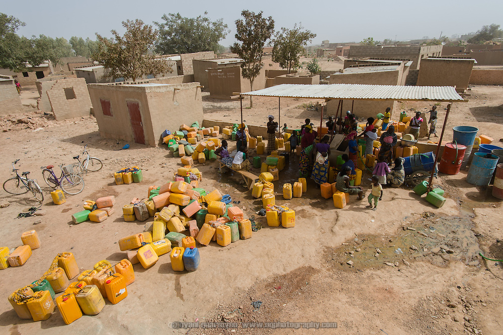 Women queueing for water at a water point in Wapassi, an informal settlement in Burkina Faso's capital, Ouagadougou, on 25 February 2016. The flow rate is low, and residents report having to wait hours for water.