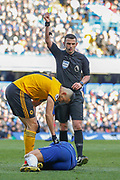 Referee Michael Oliver gives Wolverhampton Wanderers midfielder Romain Saiss (27) a yellow card after a foul on Chelsea midfielder Eden Hazard (10) during the Premier League match between Chelsea and Wolverhampton Wanderers at Stamford Bridge, London, England on 10 March 2019.