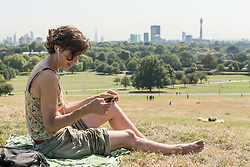 © Licensed to London News Pictures. 24/08/2016. London, UK. A woman enjoys the sunshine on Primrose Hill as a mini heatwave brings sunshine and predicted temperatures above 30C in the capital. Photo credit : Stephen Chung/LNP