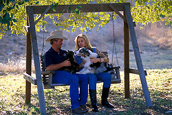 couple sitting outdoors on a swing with their pets