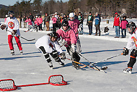 Mo Collins of the Quincy Fighin' Squirrels and Kristy Yorston of Joe's Chicks battle for the Women's Championship title Sunday afternoon during the New England Pond Hockey Classic on Lake Waukewan.  (Karen Bobotas/for the Laconia Daily Sun)