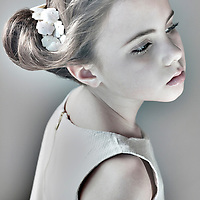 Female youth with hair tied in bun looking down