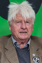 "London, UK. 9 October, 2019. Stanley Johnson, father of Prime Minister Boris Johnson, wearing an Extinction Rebellion sticker, prepares to address climate activists from Extinction Rebellion in Trafalgar Square on the third day of International Rebellion protests. He commented that the Prime Minister's characterisation of the protesters as ""uncooperative crusties"" had been made in jest and described their work as ""extremely important""."